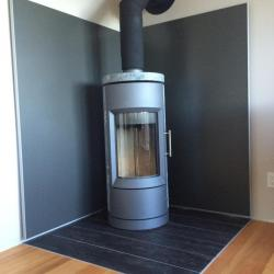 medium grey non-combustible aluminum panels behind soapstone woodstove