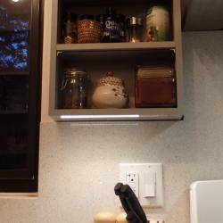Custom spice rack with under cabinet lighting next to stove
