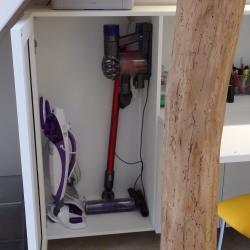 Despatx a mida sota l'escala en alumini lacat blanc amb espai per amagar l'aspiradora